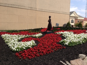 The flowers have filled in the Drunkard's Path quilt, across from the Midwest Museum of American Art.  It now looks spectacular.  That's Tuck's sculpture, Matriarch, in the center.
